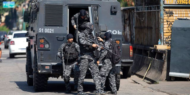 Police get out of an armored vehicle during an operation against alleged drug traffickers in the Jacarezinho favela of Rio de Janeiro, Brazil, Thursday, May 6, 2021.